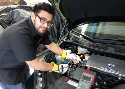 Person working on fuel cell battery in car