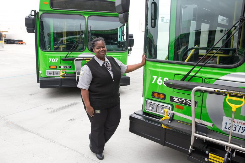 Female bus driver standing in front of two new fuel efficient busses